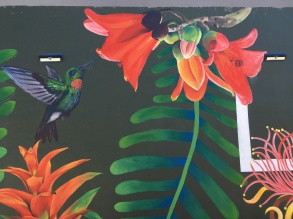 I painted the bundle of red-orange flowers. A guest artist helped out and created that beautiful hummingbird.